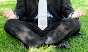 457213-business-man-in-black-suit-and-blue-tie-is-in-meditation-stance-on-green-grass